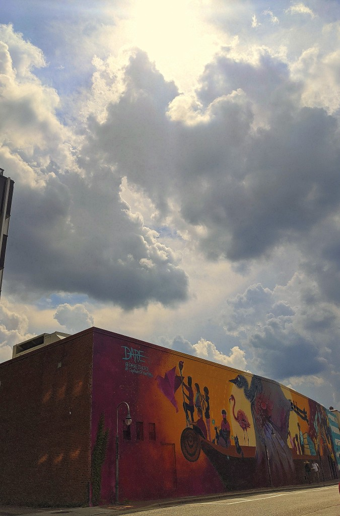 Sunlight streams through clouds over mural on Old St in downtown Fayetteville, NC.