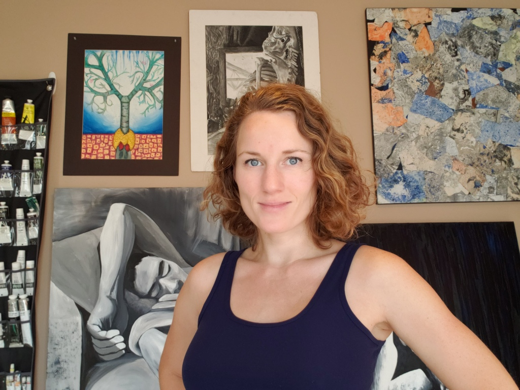 Jessilee Hari in her art studio, various paintings and collage on the wall behind her