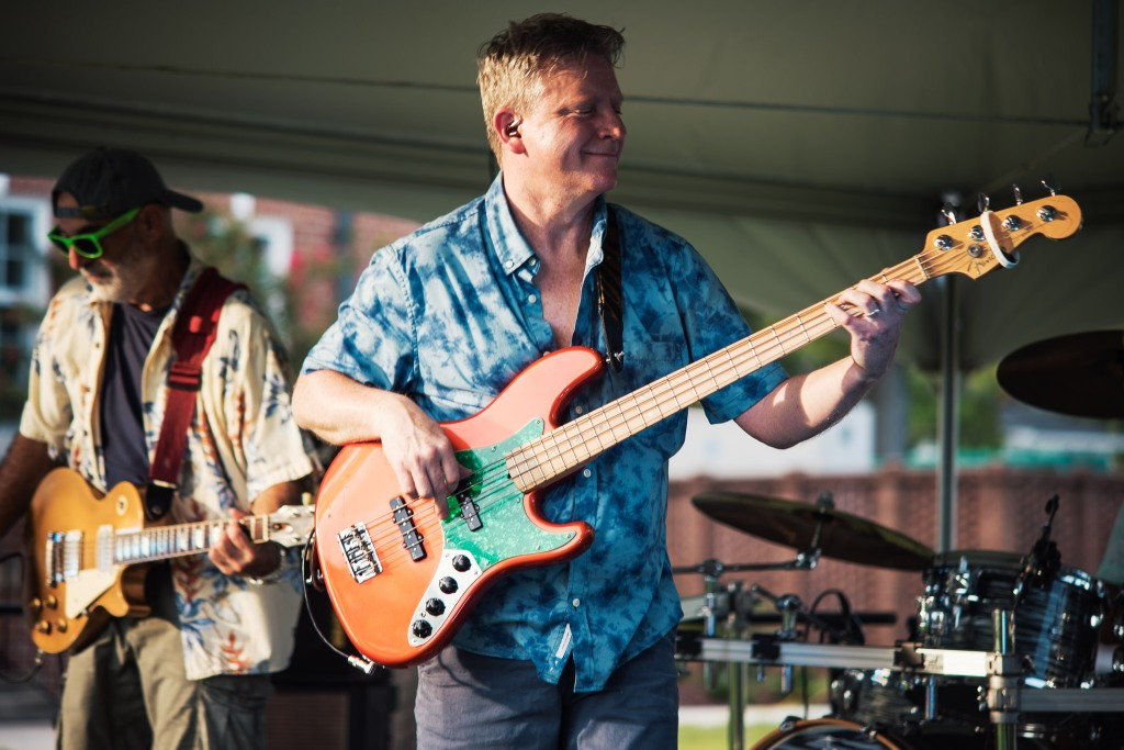 Tony wears a blue tie dye buttonup shirt and plays an orange and green bass guitar. He's standing in front of a fellow musician and a drum set, all under a large tent.